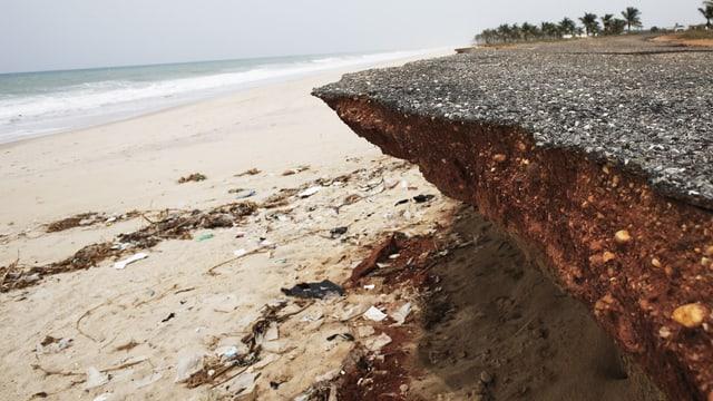 Die an den Rändern abgebrochene und unterspülte Strasse ragt über den Sandstrand.