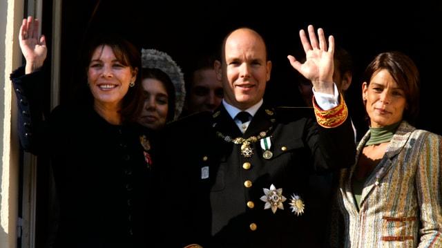 Prinzessin Caroline, Fürst Albert und Prinzessin Stéphanie winken den Einwohnern vom Balkon zu.