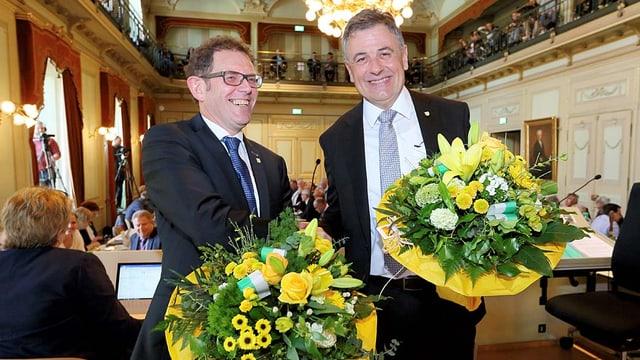 Zwei lachende Männer mit Blumenstrauss