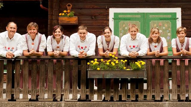 Familie lächelt vom Balkon eines alten Emmentaler Bauernhauses herab.