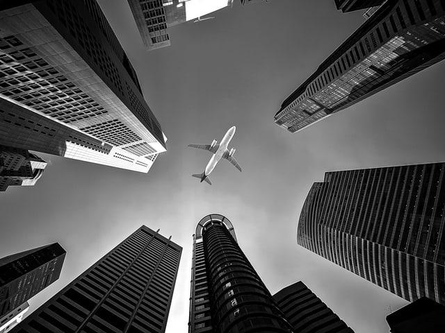 Flugzeug zwischen Wolkenkratzer von unten. Schwarzweisses Bild.