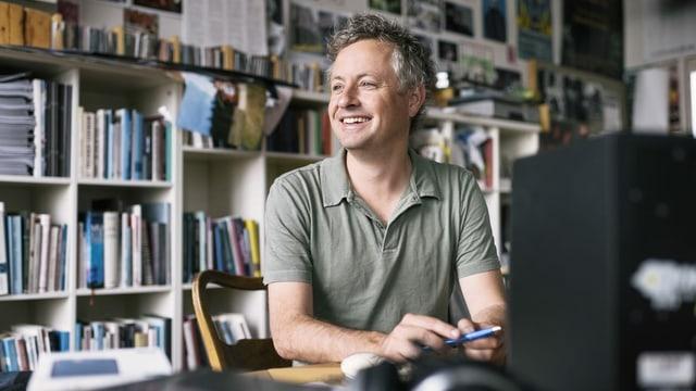 Ein Mann sitzt an seinem Pult in seinem Büro. Hinter ihm viele Bücher, CDs und Fotos.