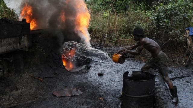 Ein Mann löscht eine Feuer einer illegalen Ölraffinerie im Nigerdelta.
