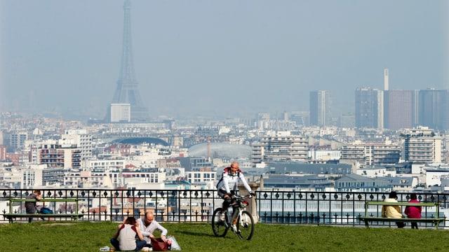 Grüne Wiese mit Radfahrer im Vordergrund, im Dunst dahinter der Eiffelturm.