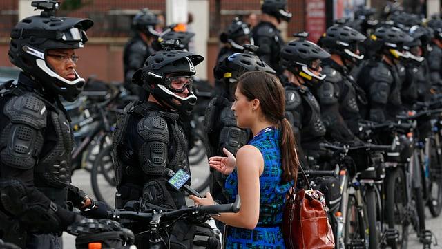 Eine Journalistin mit Mikrofon steht vor einer langen Reihe von Polizisten in schwarzer Kampfmontur.