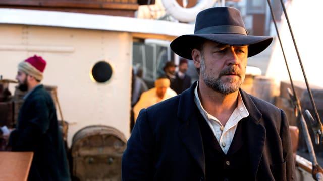 Russel Crowe steht auf einem Schiff, das halbe Gesicht ist von der Sonne beschienen.