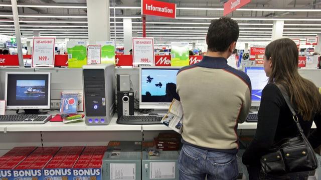 Kunden stehen in einem Medienmarkt vor dem Regal mit Computern