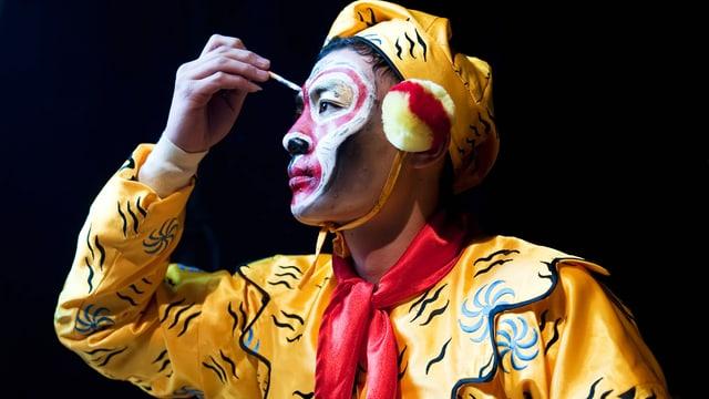 Mann in gelb-rotem Kostüm schminkt sein Gesicht weiss-rot.