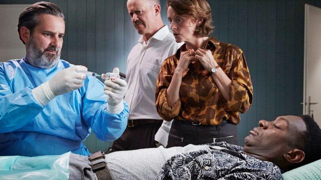 Ein schwarzer Mann liegt verwundet auf dem Bett während ein Arzt daneben eine Spritze vorbereitet.