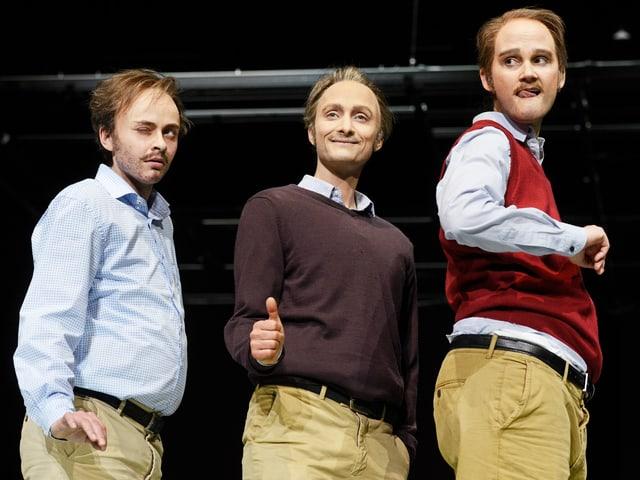 Drei Schauspielerinen in Männerkleidern posieren lachend auf einer Bühne.