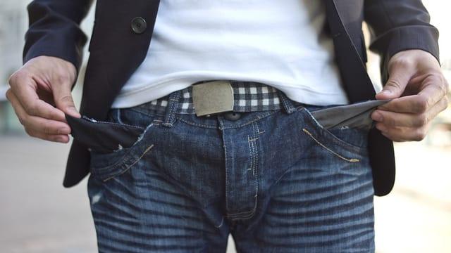 Ein Mann zeigt seine Hosentaschen, die leer sind.