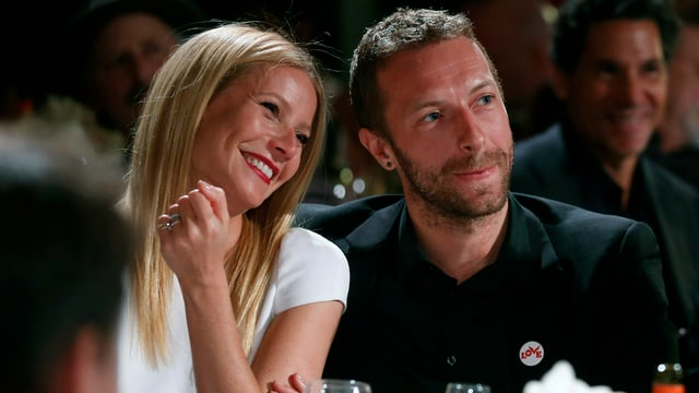Chris Martin und Gwyneth Paltrow nebeneinander an einem Tisch sitzend.