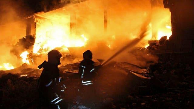 Brennendes Haus, zwei Feuerwehrleute mit Schlauch.