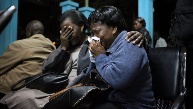 Zwei weinende Frauen sitzen auf einer Bank.
