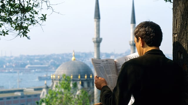 Orhan Pamuk liesst Zeitung in Istanbul.