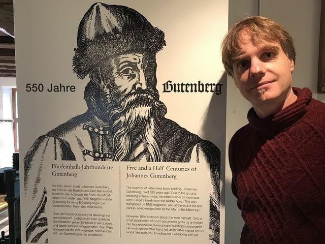 Martin Kluge neben einem Plakat mit Gutenberg.