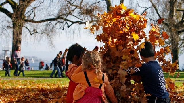 Kinder beim Spielen im Herbstlaub