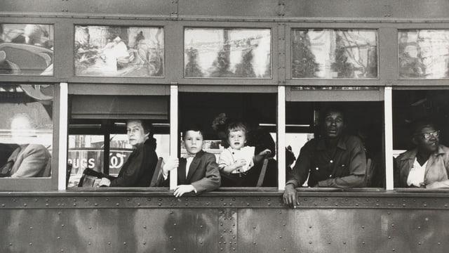Ein Bus aus dessen Fenstern Menschen schauen.