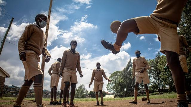 Scharze Jungen, die in Schuluniform miteinander Fussball spielen