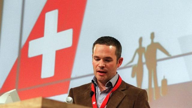 Ein Mann mit kurzen Haaren steht neben der Heckflosse eines Flugzeugs der Swiss.