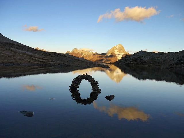 Steinbrücke im Wasser mit Spiegelung. Im Hintergrund ein Berg.