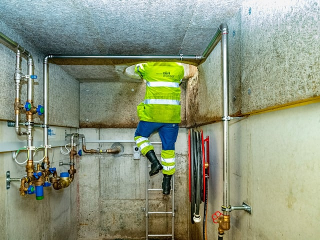 Mann steigt Leiter herunter in einen Schacht mit Wasserleitungen