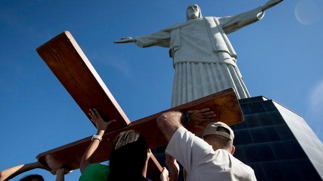 Drei Menschen errichten vor der Jesusstatue auf dem Corcovado in Rio de Janeiro das hölzerne Weltjugendtagskreuz.
