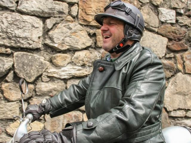 Mann mit Helm auf Moped