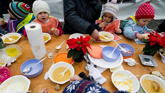 Kinder mit Kappe essen Suppe
