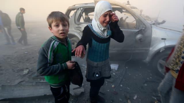 Ein Junge und ein Mädchen vor einem zerstörten Fahrzeug.