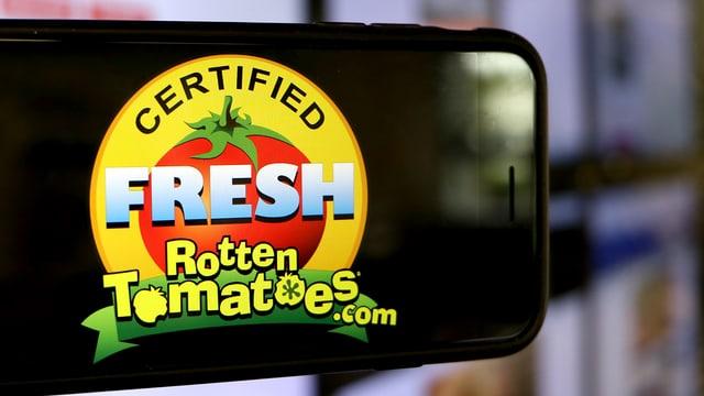 """Ein Handy mit dem Auszeichnungs-Symbol """"Certified Fresh"""" der Webseite Rotten Tomatoes auf dem Bild."""