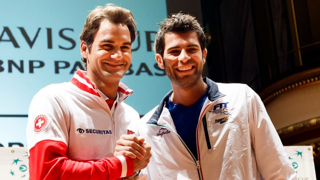 Roger Federer und Simone Bolelli reichen sich an der Auslosung des Davis-Cup-Halbfinal im September 2014 die Hand.