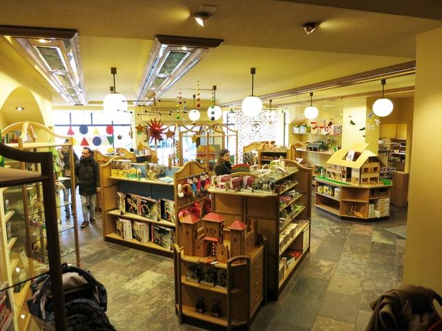 Blick in das Geschäftslokal im Erdgeschoss mit Holzburgen und Puppenhäusern.
