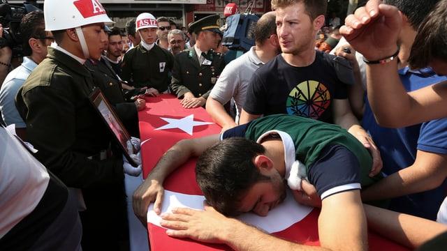 Mann liegt auf einem Sarg mit türkischer Flagge
