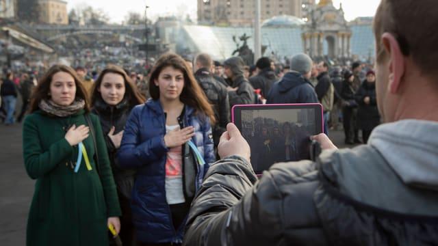 Drei junge Frauen lassen sich auf dem inzwischen friedlichen Maidanplatz fotografieren.