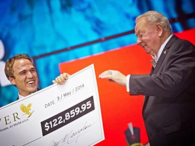 Ein älterer Mann überreicht einem lachenden, jungen Mann einen überdimensionalen Scheck.