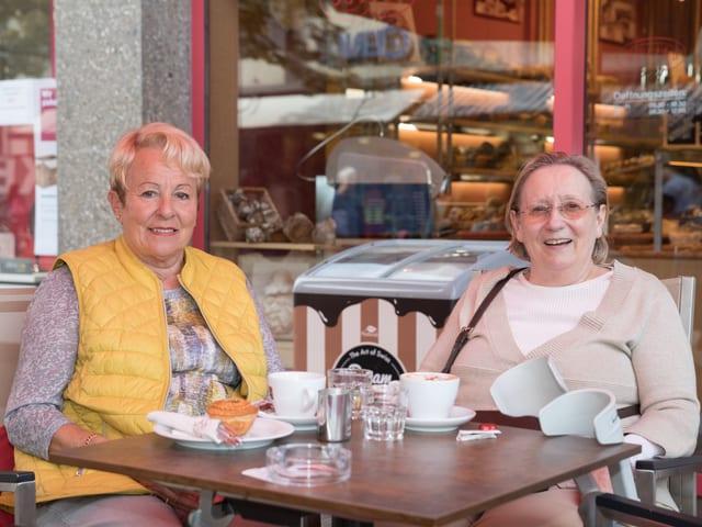 Zwei ältere Frauen sitzen lachend am Tisch einer Bäckerei.