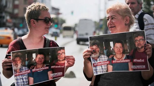 Zwei Demonstrantinnen halten Plakate hoch, darauf die drei verhafteten Journalisten.