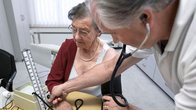 Arzt misst einer älteren Frau den Blutdruck