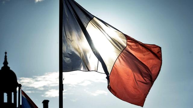 Eine französische Flagge weht im Wind vor der Sonne.