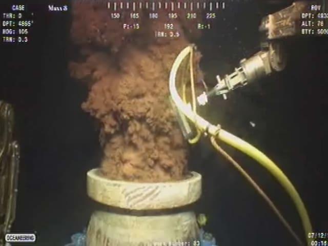Öl sprudelt aus einem Rohr unter Wasser.
