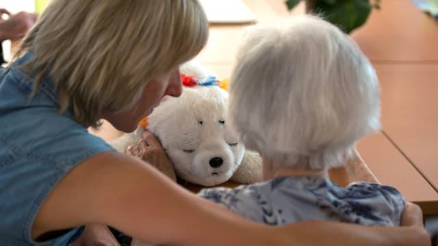 Eine Angehörige und eine Bewohnerin eines Pflegezentrums sitzen nebeneinander.