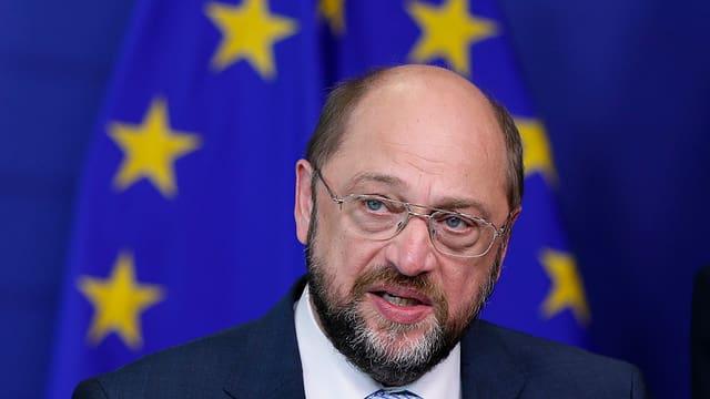 Martin Schulz, mit Brille und Bart, spricht vor der Europa-Flagge