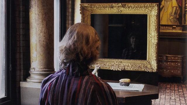 Eine Frau betrachtet ihre Reflexion in einem leeren Bilderrahmen.