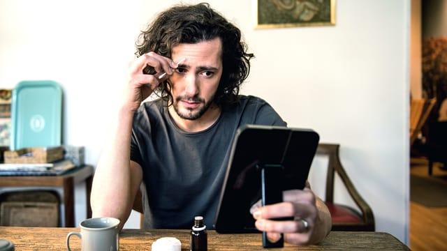 Ein Mann sitzt am Tisch schaut in einen Handspiegel und tupft sich mit einem Wattestäbchen auf die Stirn.
