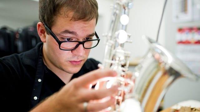 Ein junger Mann repariert ein Saxophon.
