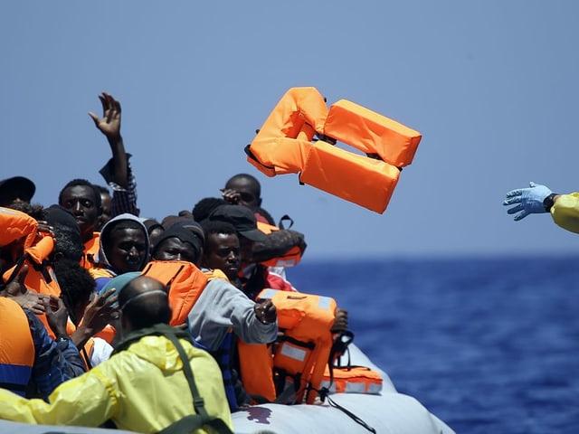 23.6.2015: Ein belgischer Soldat wirft Migranten in einem Gummiboot vom Marine-Schiff Godetia aus Schwimmwesten zu. An diesem Tag nahm alleine das belgische Schiff vor der Küste Libyens hunderte Geflüchtete auf und brachte sie an Land.