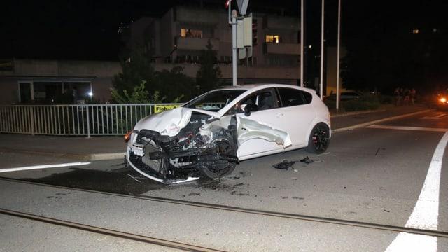 Ein weisses Auto steht mit eingedrücktem Kotflügel beim Bahnübergang kurz vor den Geleisen.