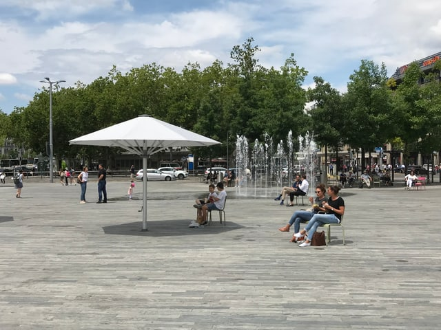 Der Sechseläutenplatz, im Hintergrund das Wasserspiel. In der Mitte ein offener, weisser Sonnenschirm.