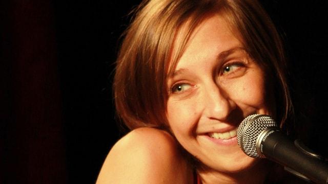 Porträt der Kabarettistin Sarah Hakenberg vor einem Mikrofon.
